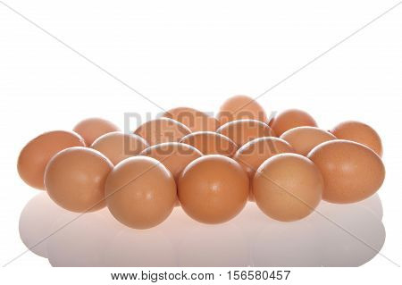 Many Organic speckled brown eggs with condensation from being cold on a reflective surface isolated on white