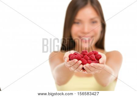 Woman holding fresh raspberries in hands closeup isolated on white background. Asian woman showing handful of red raspberries fruits in woman hands. Raspberry fruit berry healthy diet concept.