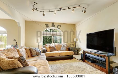Cozy Family Room Furnished With Leather Sofas With Beige Cushions.