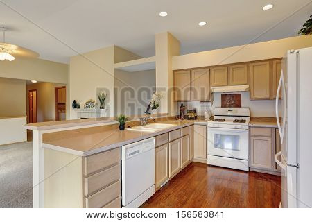 Kitchen In Creamy Tones With Hardwood Floor And White Appliances