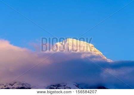 View of beautiful Alps with snow-capped mountain tops and nice clouds at sunset.