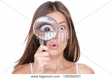 Funny expression. Shocked woman looking through a magnifying glass. Surprised Asian girl looking astonished discovering clues with big eyes through a magnifying glass, isolated on white background.