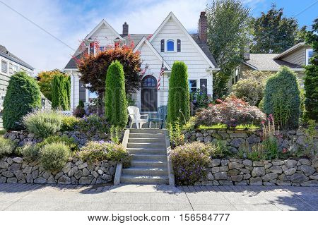 American craftsman style home with beautiful landscape design trimmed shrubs rocks and flowers. Northwest USA
