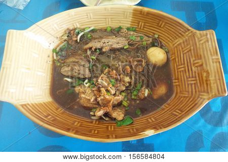 Boat noodle on brown plate on table