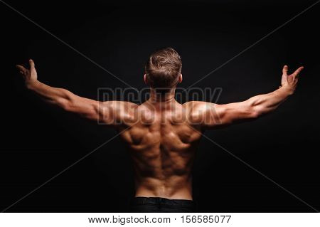 Bodybuilder posing on a black background. Dramatic portrait of an athlete. Drying. Relief and sculptural muscles of the body. Healthy lifestyle concept. The muscles of the shoulders and back.