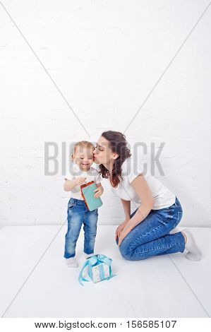 Mother kisses the daughter. Little girl holding wallet. Mother and daughter dressed in jeans and white T-shirts. Family.
