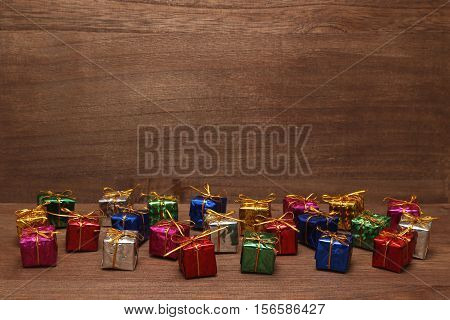 Many colorful gift boxes with gold ribbons on wood.