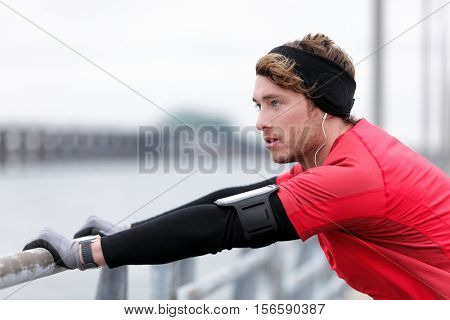 Young man runner doing running warm-up before winter run in city outdoor. Athlete wearing smartwatch, phone armband for music and warm sportswear for cold weather: Gloves, headband, long underwear.
