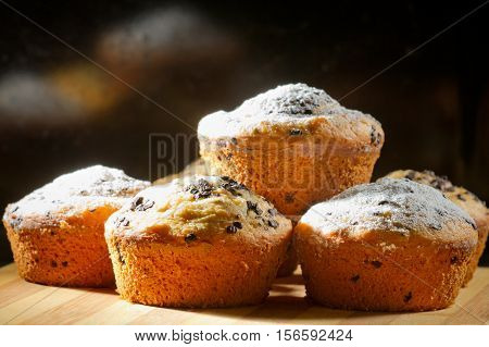 Some creamy muffins with caster sugar on black background