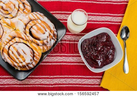 Cinnamon brioche with strawberry jam and milk on rustic background