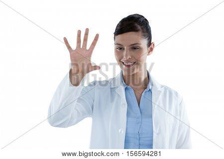 Beautiful female doctor using digital screen against white background