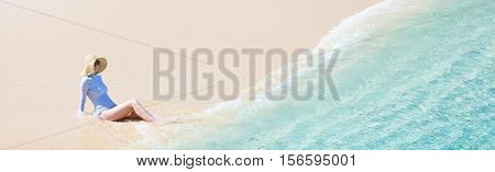 panorama of young woman in sunhat and rashguard or swimsuit enjoying perfect caribbean beach sun protection concept