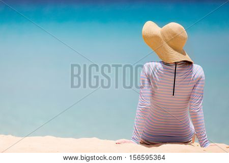 back view at young woman at the beach in sunhat and rashguard or swimsuit enjoying perfect caribbean sea sun protection concept