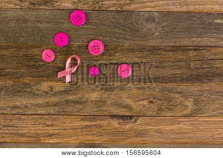 Womens health symbol in pink ribbon on wooden board.