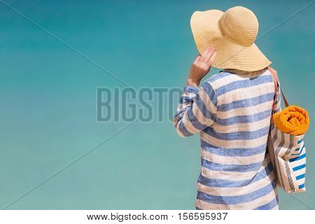 back view at young woman at the beach in sunhat and cover enjoying perfect caribbean sea sun protection concept