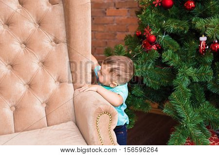 Little baby boy standing near the Christmas tree. Year-old child waiting New Year 2017, happy family concept.