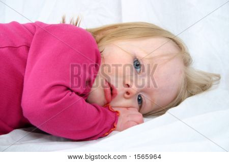 Cute Little Girl Laying On A White Background