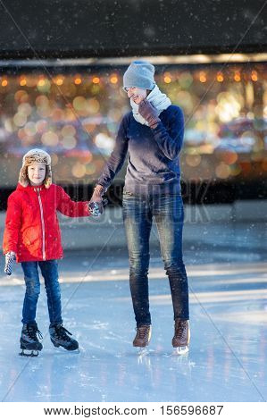 family of two enjoying ice skating at winter at outdoor skating rink at snowy weather winter and family concept