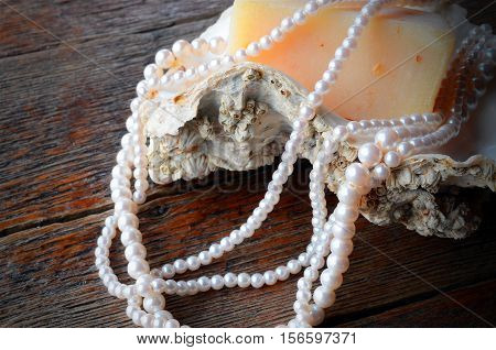 A close up image of a string of pearls on an oyster shell with a bar of homemade oatmeal soap.