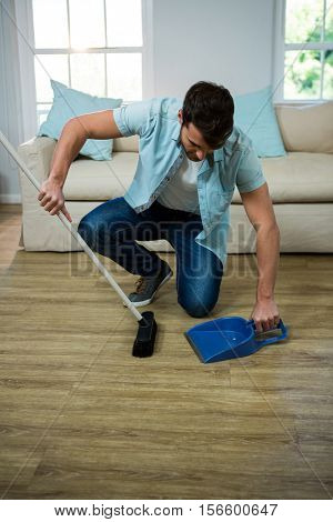 Man cleaning the floor with broom and dust picker at home