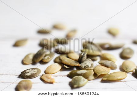Pumpkin seeds on white background close-up. Texture of squash semen, agricultural backdrop