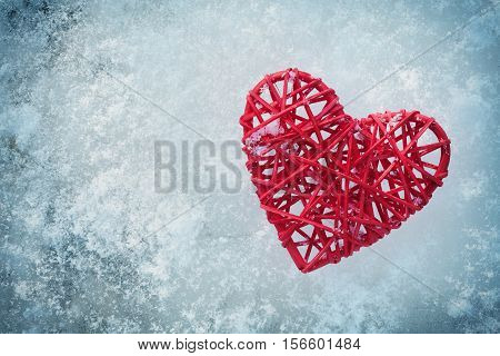 Red heart on the background of ice on a winter day from above. Valentines or mothers day holiday concept.