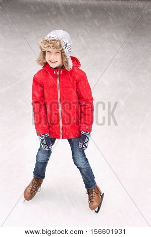 little boy enjoying ice skating at winter at outdoor skating rink at snowy weather winter concept
