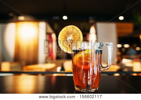 Glass of tasty citrus on restaurant table. Hot drink with orange slice. Bar, party, recipe, refreshment , winter beverage concept