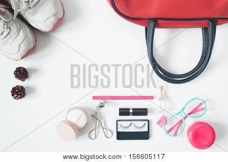 Overhead view of essential beauty items Top view of red hand bag fashion eyeglasses cosmetics and sneakers top view isolated on white background