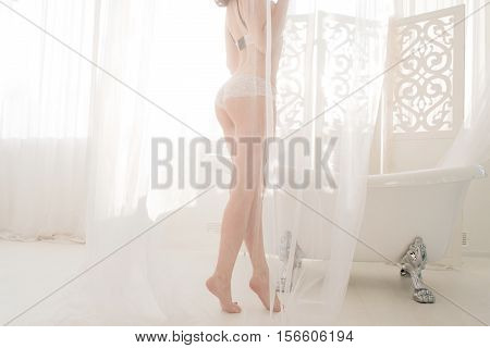 Silhouette of nude woman in bathroom. Sexy lady in white lingerie standing behind diaphanous fabric near bath, free space