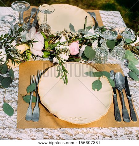 Table setting for banquet with flowers, void. Catering serving outdoor for rustic wedding, beautifully decorated place for person in autumn style