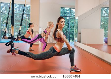 Young attractive women do suspension training with fitness straps in the gym's studio