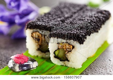 Maki Sushi with Prawn, Cucumber and Fried Seafood inside. Topped with Black Tobiko (flying fish roe). Served on Banana Leaf with Flowers