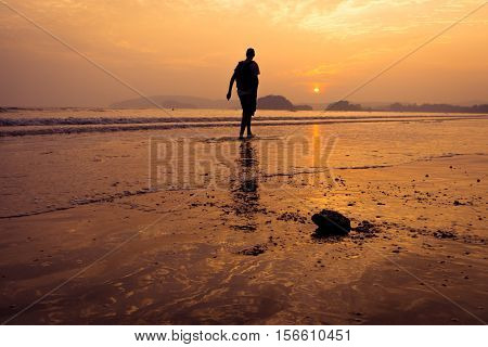 Silhouette of men walking on the beach at sunset