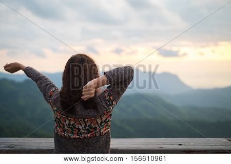 Young woman stretching on balcony with mountain view in early winter morning.