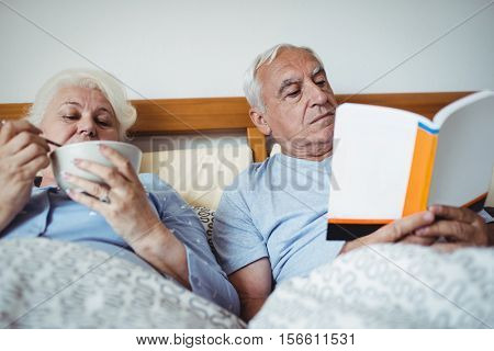 Senior man reading novel and woman having breakfast in bedroom