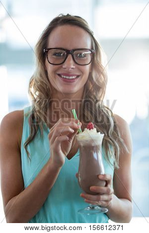Portrait of woman drinking milkshake with a straw in cafe