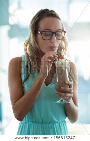 Smiling woman drinking milkshake with a straw in cafe