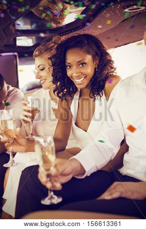Well dressed woman drinking champagne in limousine against flying colours