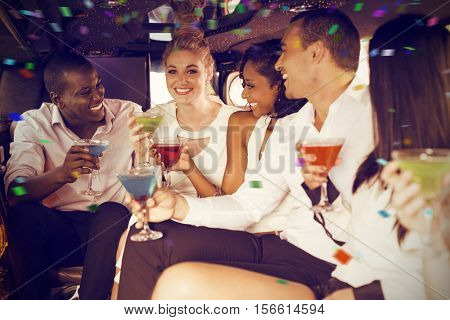Well dressed people drinking cocktails in limousine against flying colours