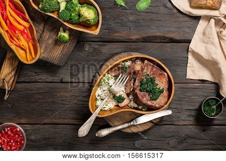Juicy sliced grilled beef steak with garnish of rice in wooden plate on dark wooden table top view