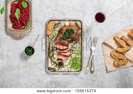 Sliced grilled beef steak on the old iron tray on light stone surface top view
