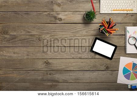 Tablet with blank screen on wooden desk with office objects top view