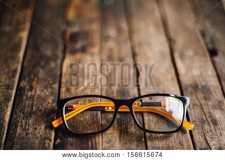 Glasses  Lie On The Dark Wooden Table.   Black Orange  Glasses