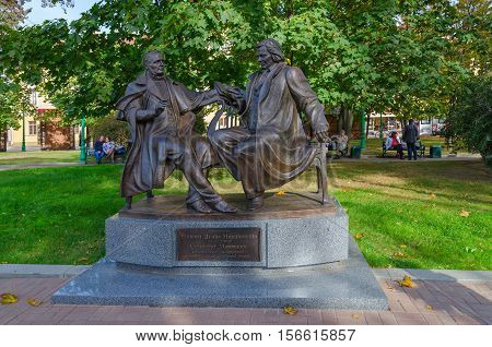 MINSK BELARUS - OCTOBER 1 2016: Unidentified people are relaxing in park near monument to playwright Vincent Dunin-Marcinkevich and composer Stanislaw Moniuszko (founders of Belorussian national classical opera)