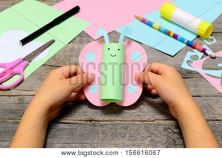 Kid holding colored paper butterfly in hands. Little kid shows a fun paper diy. Stationery on an old wooden table. Preschool paper and glue crafts activities. Children creative potential development