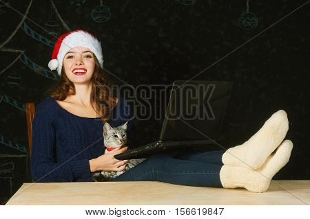 Girl with a cat and a laptop on a dark background. Merry Christmas