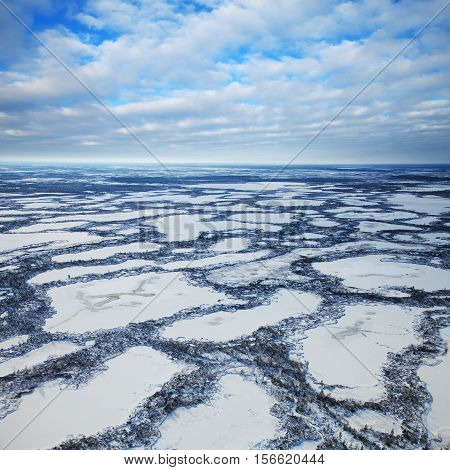 Aerial view swampy area during frosty winter day.