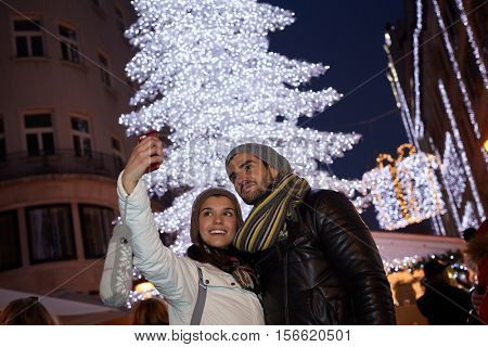 Young couple making selfie outdoors front of huge christmas tree.