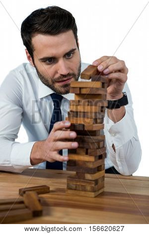 Businessman placing wooden block on a tower against white background